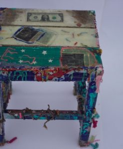 This represents the best in weird furniture. Perfect for collage seekers and art lovers. Tons of detail here. This table has lots of areas to touch delicately. There is fabric and tons of other fun stuff hanging off of it including money, yarn, amazon wood , metal bearings. Tons of colors here such as yellow, blue, white etc.....